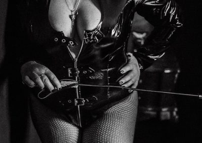 Mistress M holding a whip and waiting for you